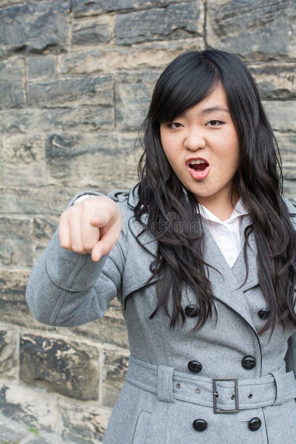 Mujer enojada por una pared de piedra imagen de archivo