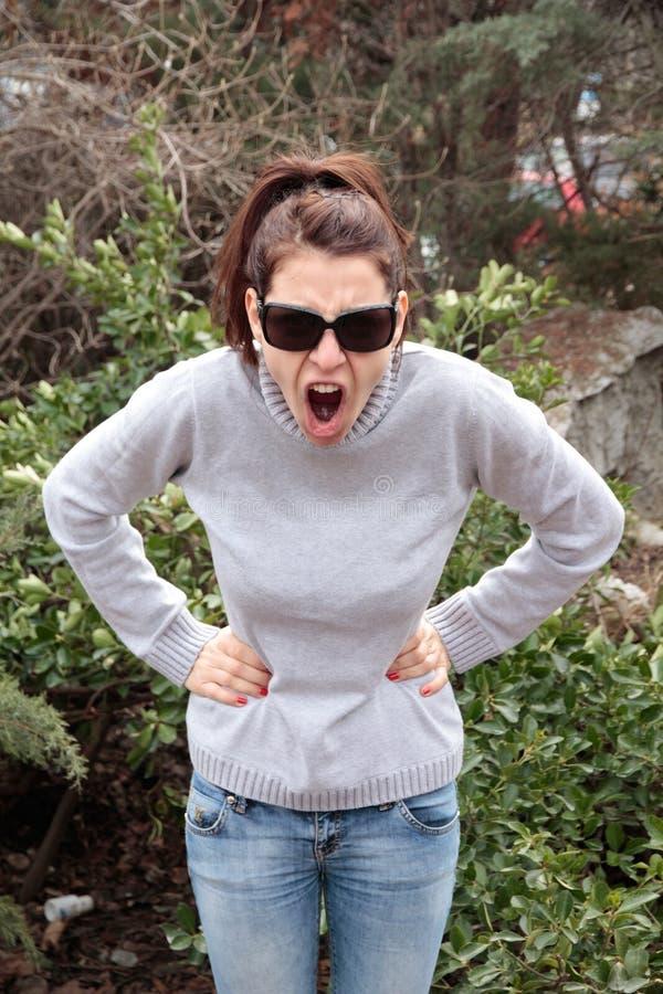 Mujer enojada que grita con los brazos en la cintura imagenes de archivo