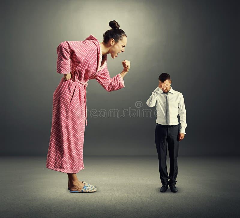 Mujer enojada que grita en el hombre cansado fotos de archivo