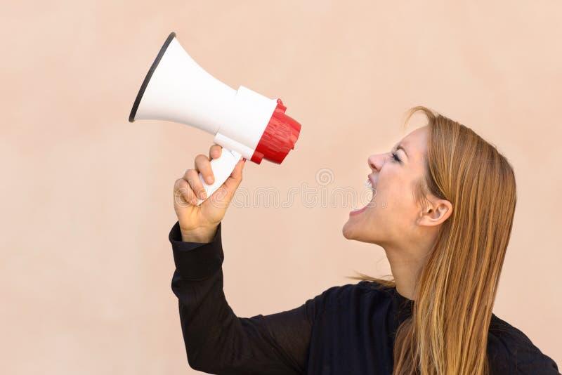Mujer enojada que grita en un megáfono fotos de archivo libres de regalías