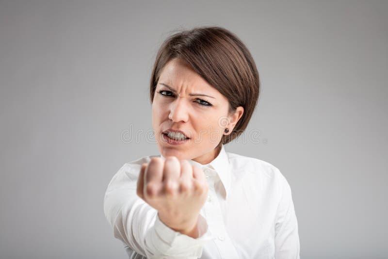 Mujer enojada que sacude su puño en la cámara foto de archivo libre de regalías