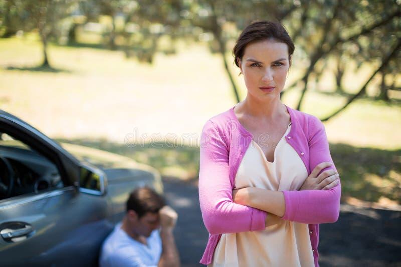 Mujer enojada que se coloca con el hombre que se sienta en coche de la avería imagenes de archivo
