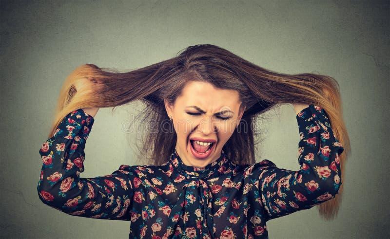 Mujer enojada que tira de su pelo hacia fuera que grita fotos de archivo