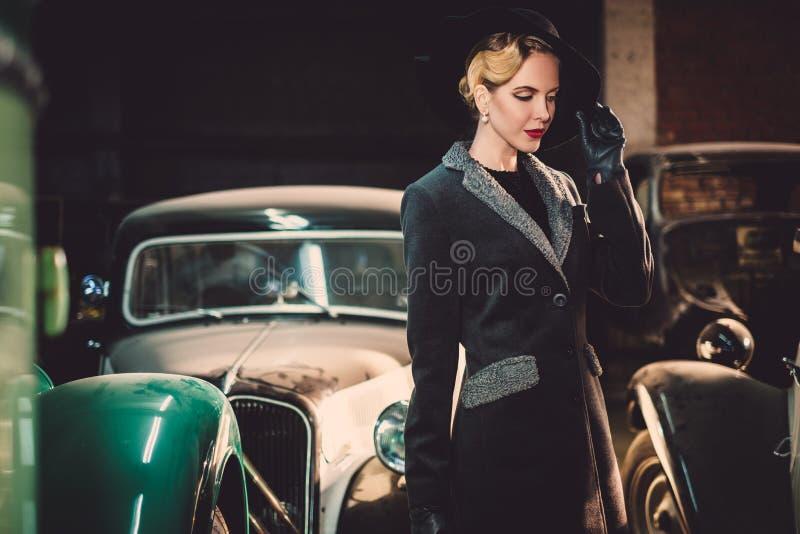 Mujer entre los coches retros en garaje foto de archivo