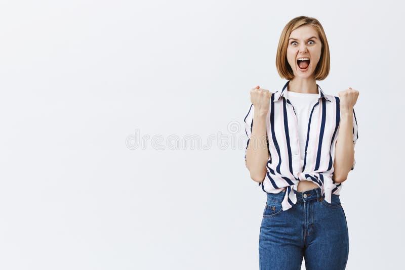 Mujer entusiasta divertida en la blusa rayada, haciendo la cara intensa mientras que grita hacia fuera ruidosamente, puños de apr foto de archivo libre de regalías