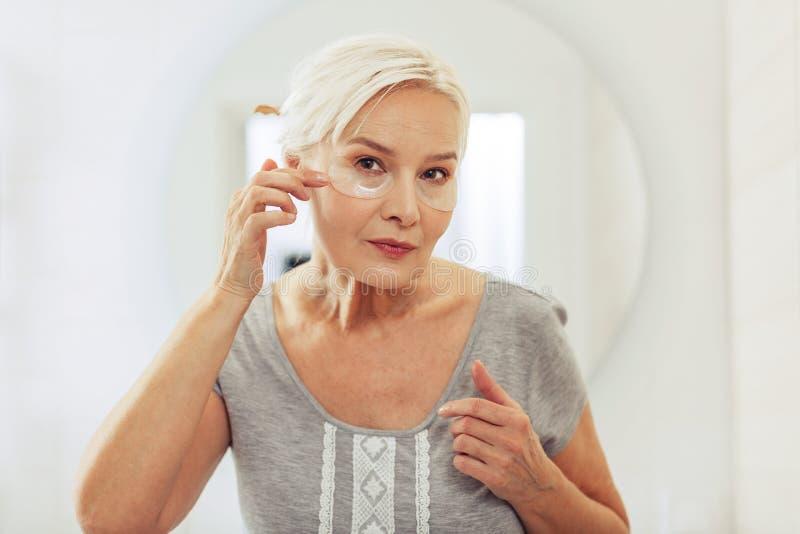 Mujer envejecida agradable que mira su cara imagen de archivo libre de regalías