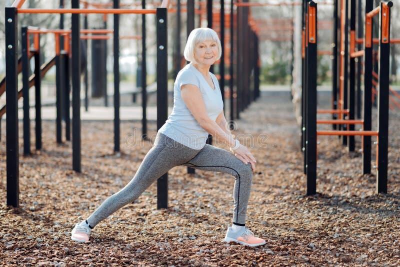 Mujer envejecida alegre que ejercita al aire libre imagen de archivo libre de regalías