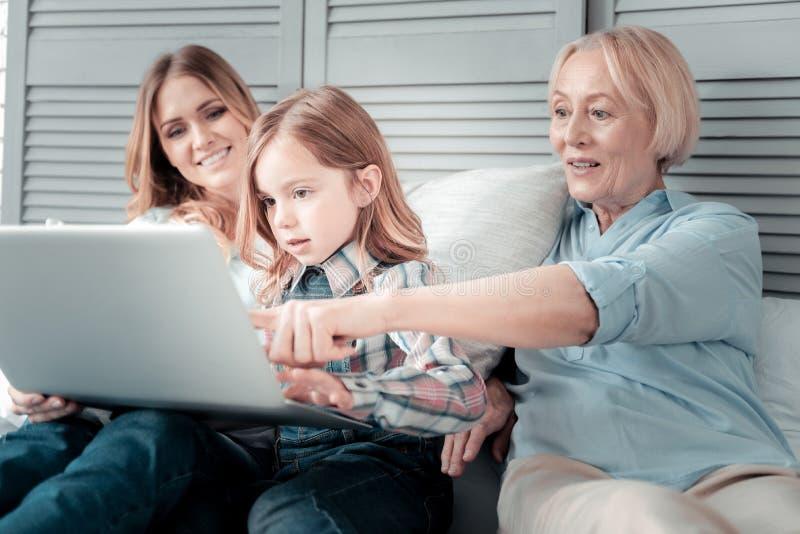 Mujer envejecida alegre que señala en la pantalla del ordenador portátil fotos de archivo libres de regalías