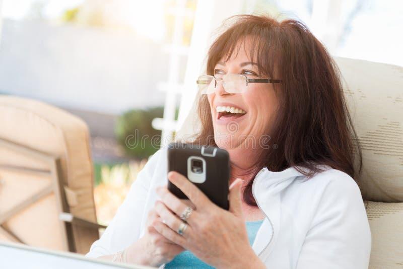 Mujer envejecida centro atractivo que ríe mientras que usa su Phon elegante imagen de archivo libre de regalías