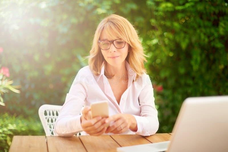 Mujer envejecida centro confiado que trabaja de hogar imagen de archivo