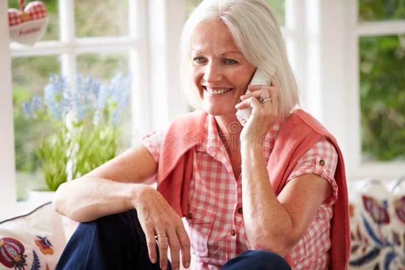 Mujer envejecida centro en casa que habla en el teléfono foto de archivo