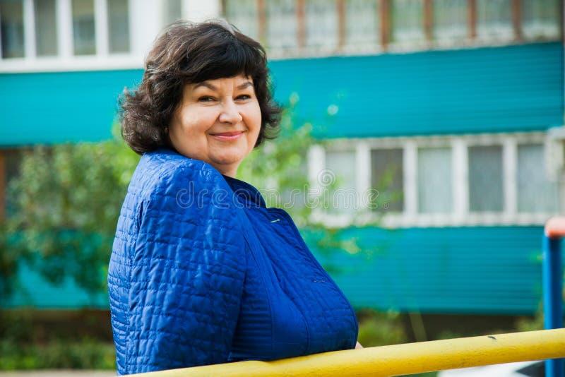 Mujer envejecida centro entre construcciones de viviendas de la ciudad fotografía de archivo