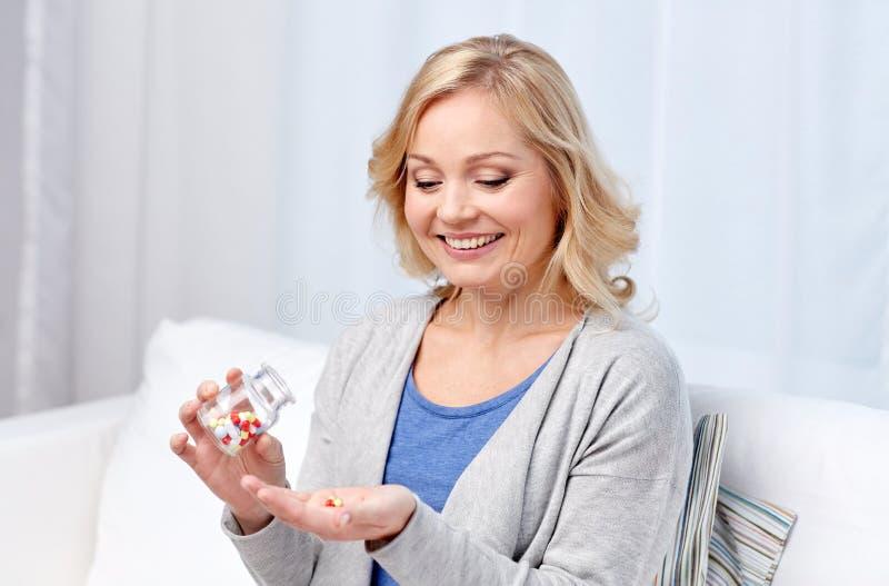 Mujer envejecida centro feliz con la medicina en casa foto de archivo
