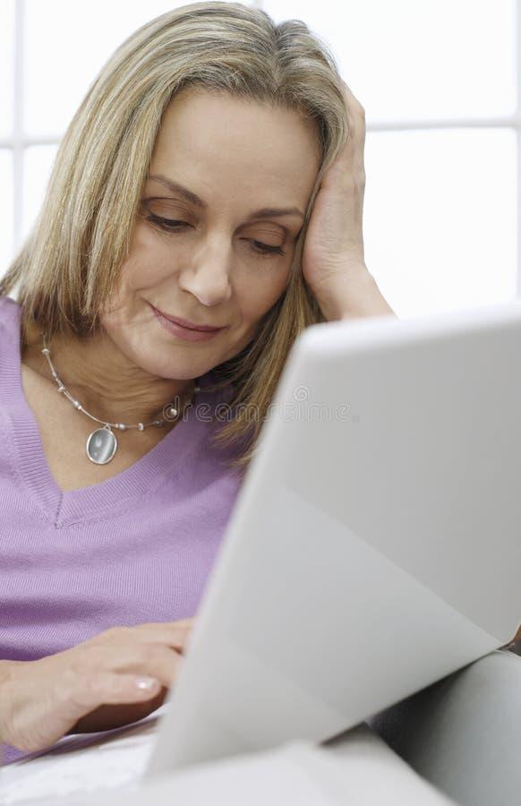 Mujer envejecida centro que usa el ordenador portátil foto de archivo libre de regalías