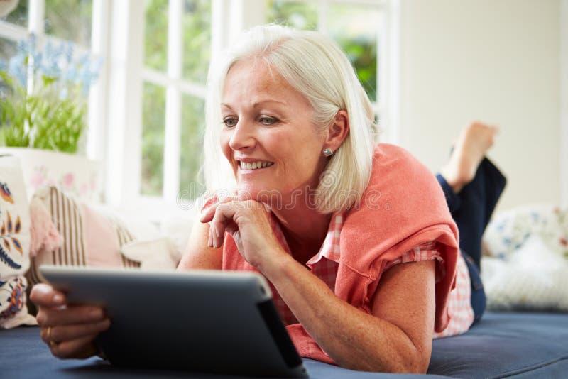 Mujer envejecida centro que usa la tableta de Digitaces que miente en el sofá fotos de archivo