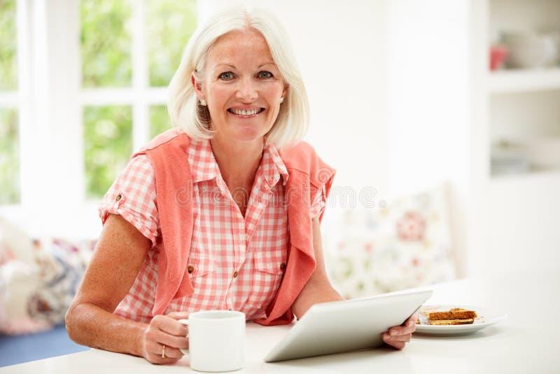 Mujer envejecida centro que usa la tableta de Digitaces sobre el desayuno fotografía de archivo libre de regalías