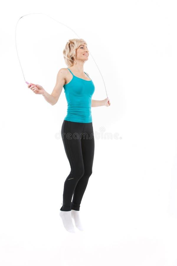 Mujer envejecida con la cuerda de salto en blanco imagen de archivo libre de regalías