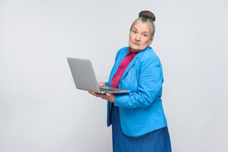 Mujer envejecida confusa que coloca y que sostiene el ordenador portátil foto de archivo libre de regalías