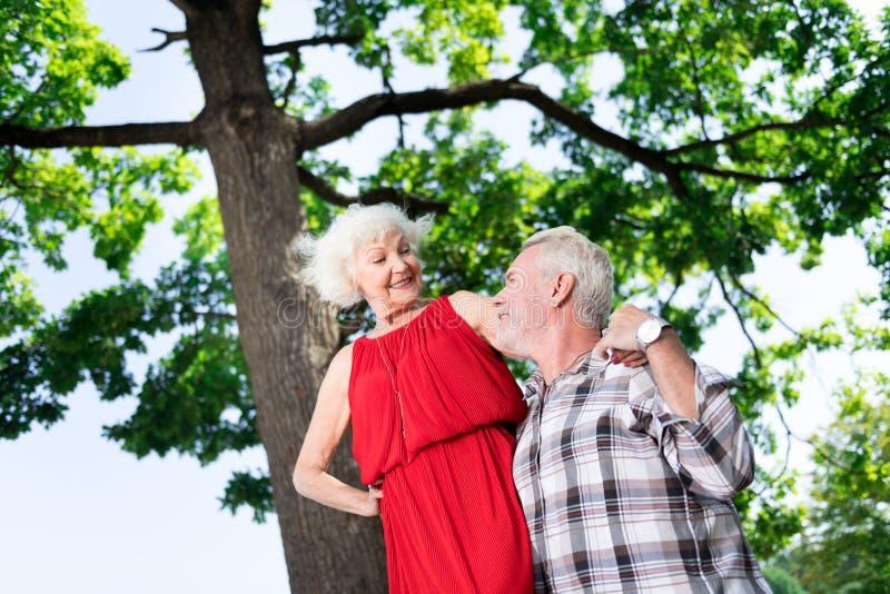 Mujer envejecida elegante que lleva el vestido rojo y los accesorios que miran a su hombre foto de archivo libre de regalías
