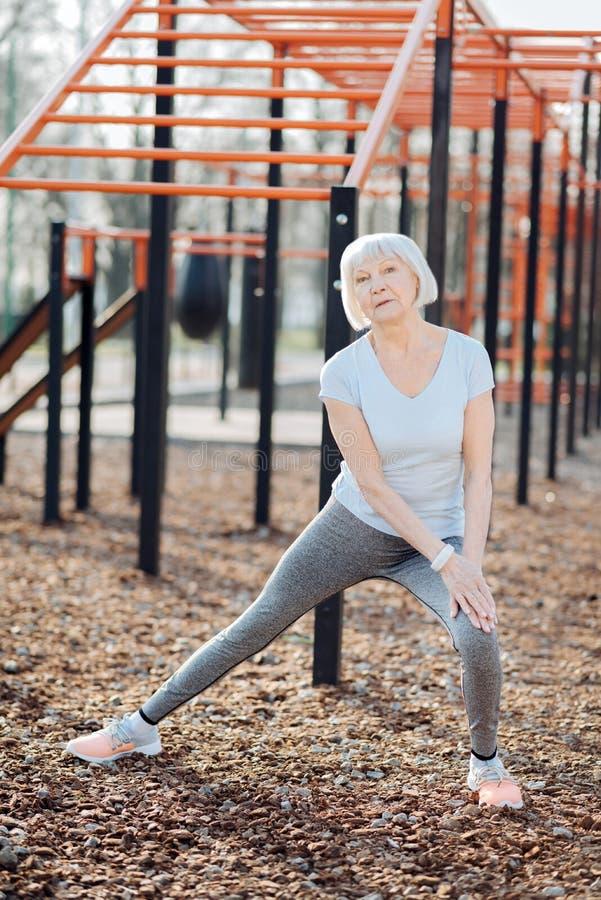 Mujer envejecida feliz que ejercita al aire libre foto de archivo