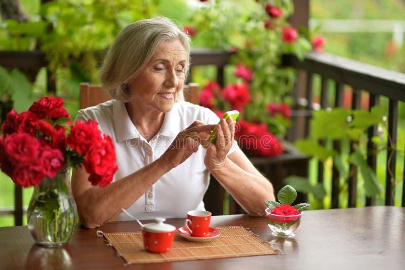 Mujer envejecida feliz que usa smartphone mientras que bebe el café foto de archivo