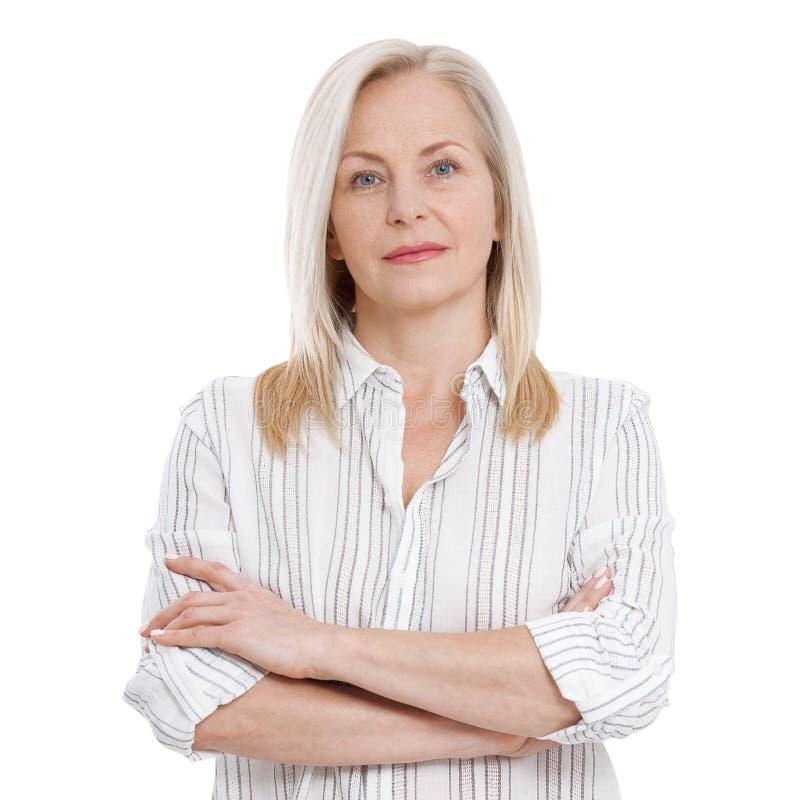 Mujer envejecida media atractiva con los brazos doblados aislados en el fondo blanco foto de archivo