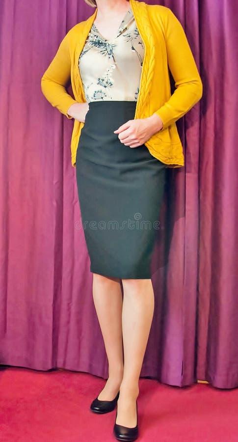 Mujer envejecida media elegante vestida que lleva una rebeca amarilla y una falda negra del lápiz foto de archivo