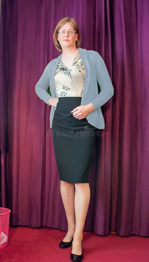 Mujer envejecida media elegante vestida que lleva una rebeca azul y una falda negra del lápiz foto de archivo