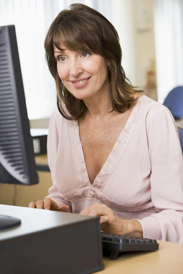 Mujer envejecida media en un ordenador foto de archivo libre de regalías