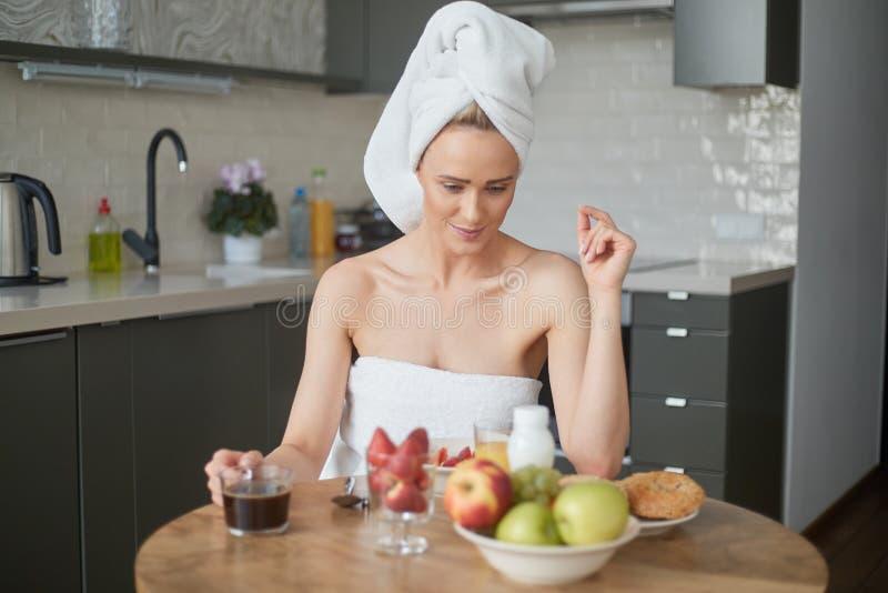 Mujer envejecida media hermosa que se sienta en su cocina por la mañana fotografía de archivo libre de regalías