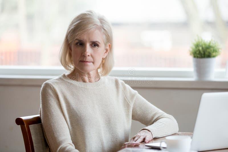Mujer envejecida media pensativa que se sienta en la tabla cerca del ordenador portátil foto de archivo libre de regalías