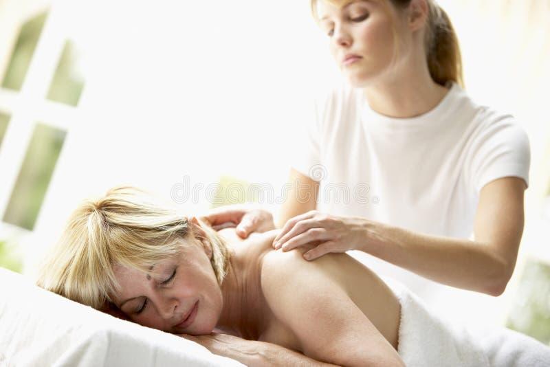 Mujer envejecida media que disfruta de masaje fotografía de archivo