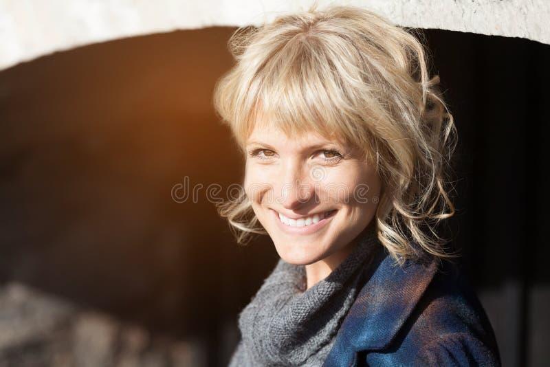 Mujer envejecida media que sonríe en la cámara afuera foto de archivo libre de regalías