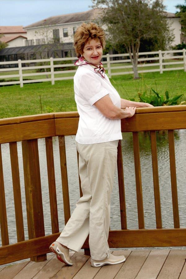 Mujer envejecida media sonriente ocasional imágenes de archivo libres de regalías