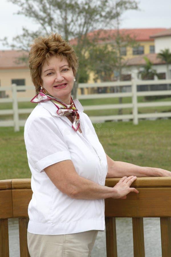 Mujer envejecida media sonriente ocasional imagenes de archivo
