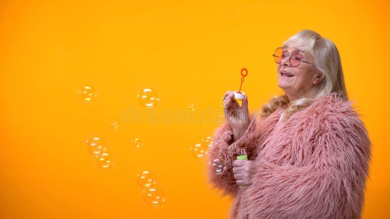 Mujer envejecida positiva en capa rosada divertida y las gafas de sol redondas que hacen burbujas de jab?n imágenes de archivo libres de regalías