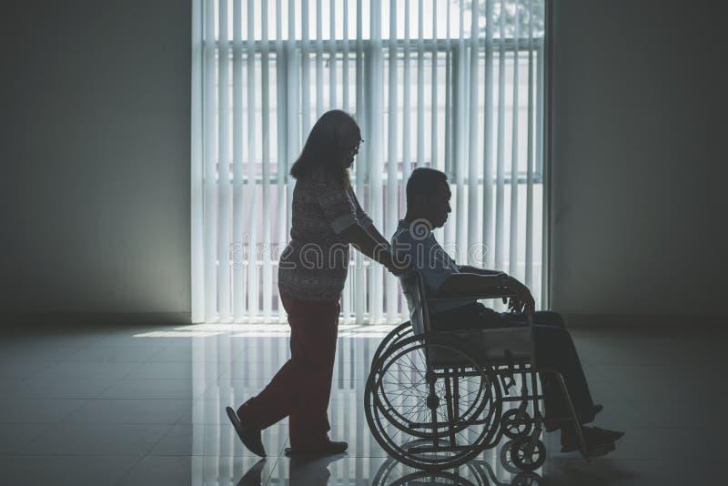 Mujer envejecida que empuja a su marido en la silla de ruedas imágenes de archivo libres de regalías