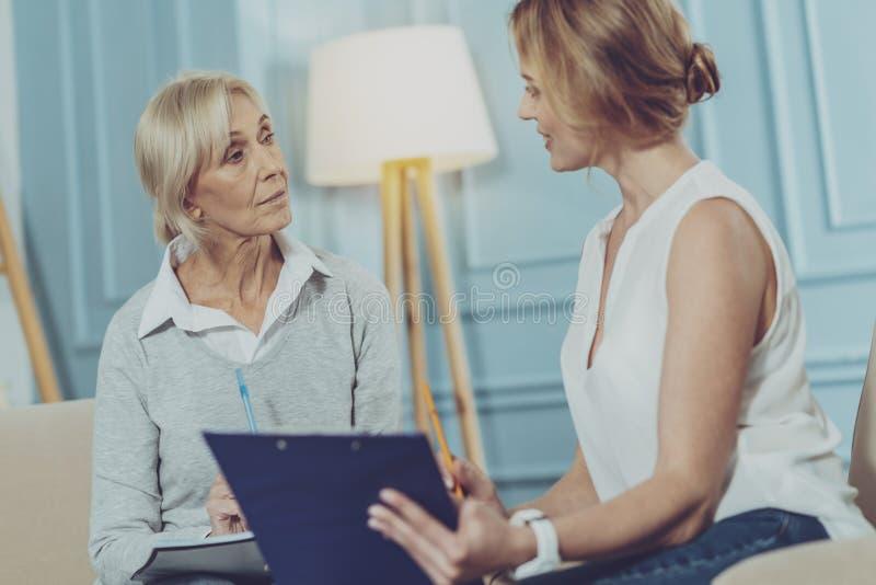 Mujer envejecida que escucha su consejero financiero fotografía de archivo libre de regalías
