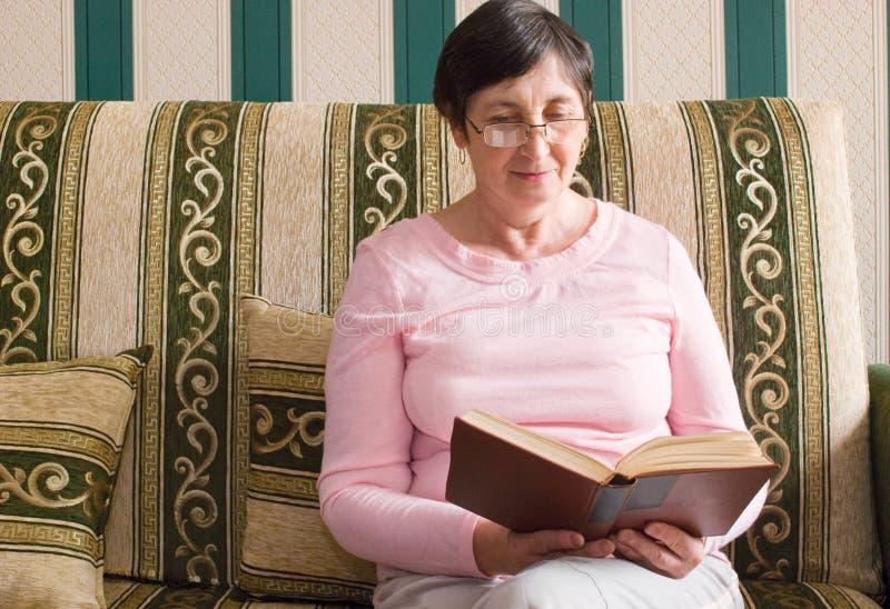 Mujer envejecida que lee un libro imagenes de archivo