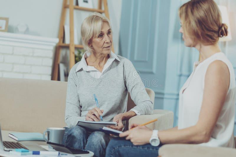 Mujer envejecida que tiene discusión con su consejero financiero fotos de archivo