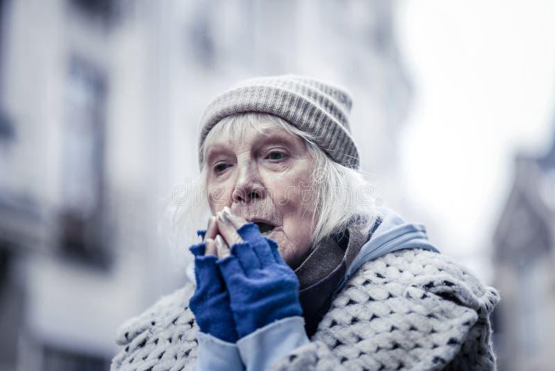 Mujer envejecida triste que intenta calentarse las manos imagen de archivo