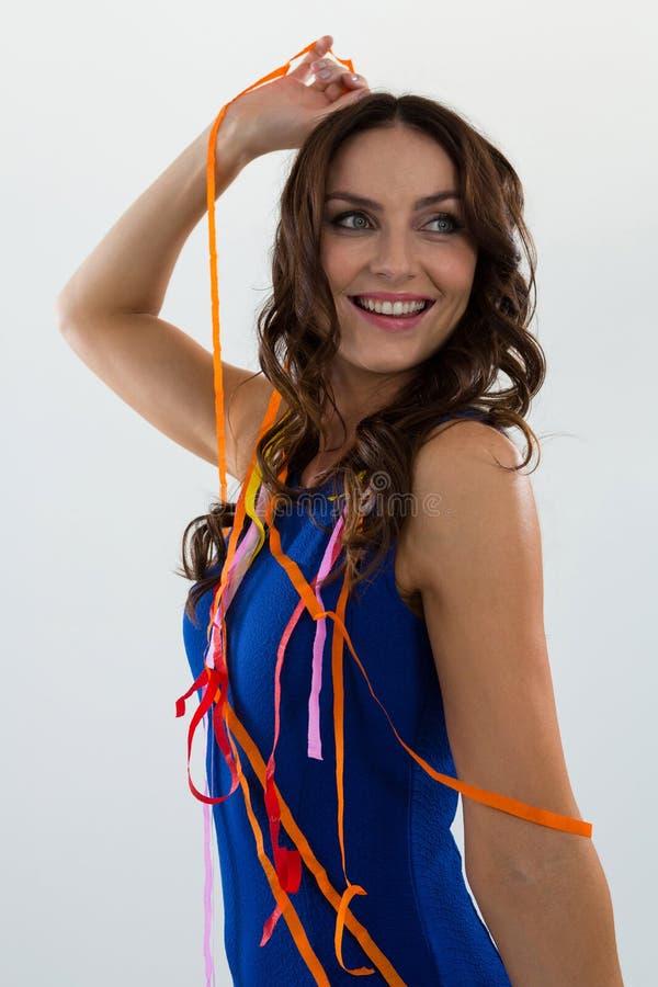 Mujer envuelta en las flámulas del multicolor que presentan contra el fondo blanco imagen de archivo libre de regalías