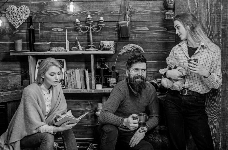 Mujer envuelta en libro de lectura combinado de lana Hombre barbudo alegre en equipo retro que bebe el vino reflexionado sobre mi imagen de archivo libre de regalías