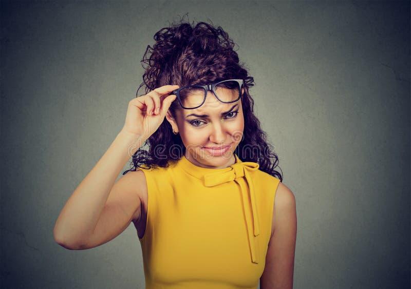 Mujer escéptica dudosa que piensa mirándole con la desaprobación imagenes de archivo