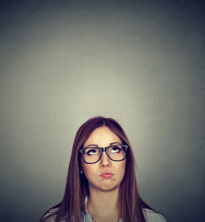 Mujer escéptica joven enfadada que mira para arriba fotografía de archivo libre de regalías