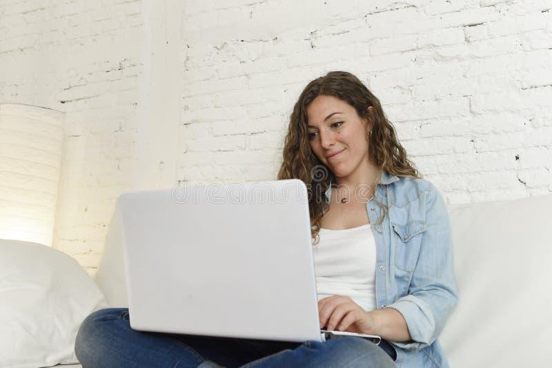 Mujer española atractiva joven que usa el ordenador portátil que sienta el trabajo relajado en el sofá casero foto de archivo libre de regalías