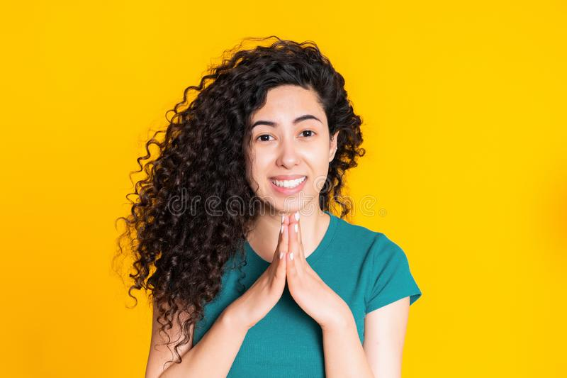 Mujer espa?ola atractiva en camiseta verde que ruega sobre fondo amarillo Muchacha de la raza mixta que pide alguien fotografía de archivo libre de regalías