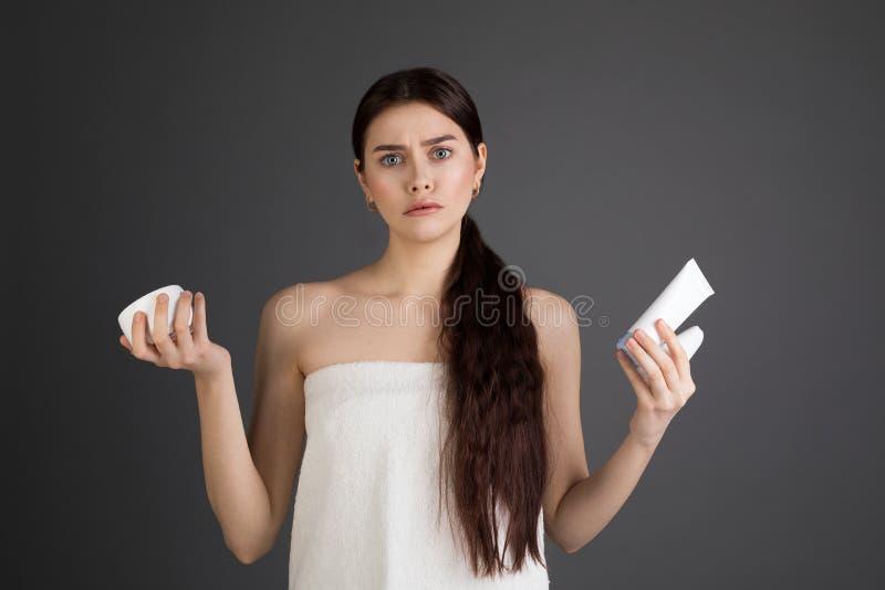 Mujer europea desconcertada dudosa insegura con el pelo moreno en toalla de baño foto de archivo