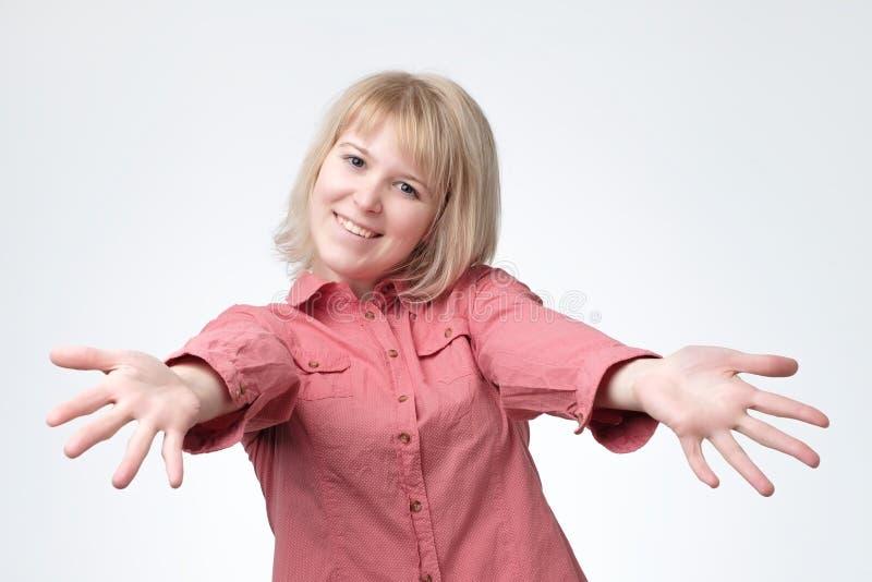 Mujer europea en camisa rosada con el apretón de manos estirado de las manos Ella quiere abrazar a sus amigos foto de archivo libre de regalías