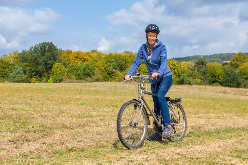 Mujer europea en la bici de montaña en naturaleza alemana fotos de archivo